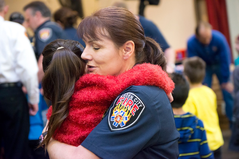 Firefighter Susan Davis embraces Crystal as she gets a new jacket for the cold winter. At Heritage Elementary in Ogden. January 17 2014. (Brian Wolfer Special to the Standard-Examiner)