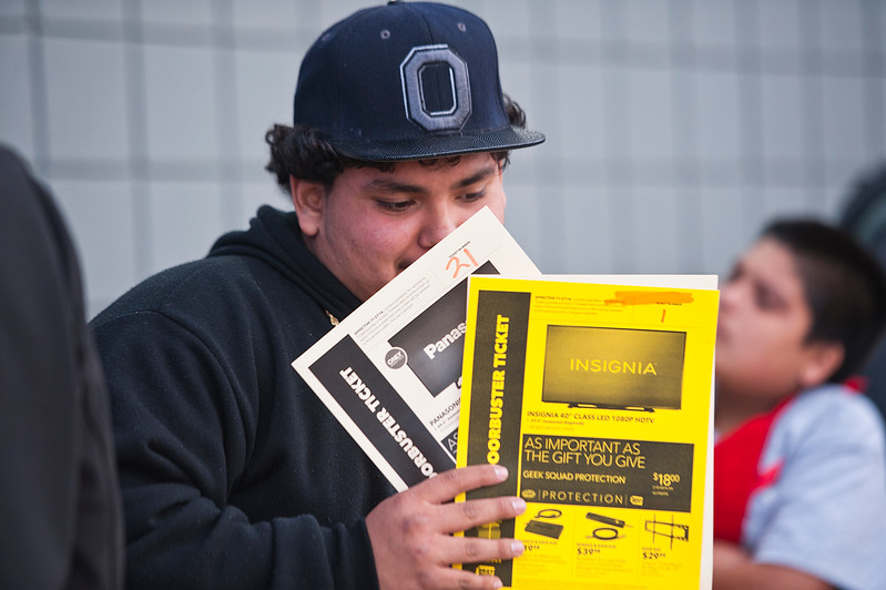 Christian Flores waits in line for the Best Buy Grey Thursday sale. He already got his ticket to get a 50in flatscreen tv. In Riverdale. On November 27 2014.
