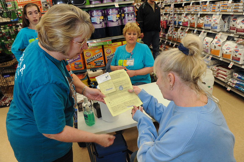 Julia Despain explains the paper work to new pet owner Sheri Windberry. At a Layton Petco. On November 30 2013. (Brian Wolfer Special to the Standard-Examiner)