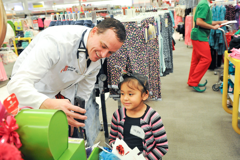 M.D Alaxander Larson enjoys his day with young haidee. Ogden Clinic holding its second annual Shop with a Doc event. Health care workers take 50 needy children shopping for Christmas. At Target in Riverdale. On December 7 2013.(Brian Wolfer Special to the Standard-Examiner)