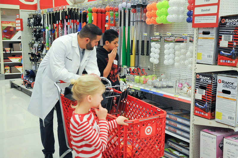 M.D Chad Tingey looks through sporting goods to help find Julio Gutierrez proper equipment for sports. At Target in Riverdale. On December 7 2013.(Brian Wolfer Special to the Standard-Examiner)