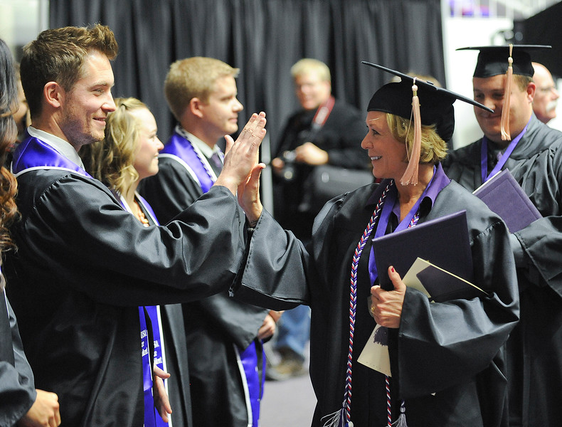 Happy student high fives classmates after she receives her degree at WSU. At Dee Events Center, on December 13 2013.(Brian Wolfer Special to the Standard-Examiner)
