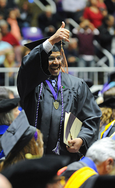 happy student gives his family a thumbs up after receiving his diploma. At Dee Events Center, on December 13 2013.(Brian Wolfer Special to the Standard-Examiner)