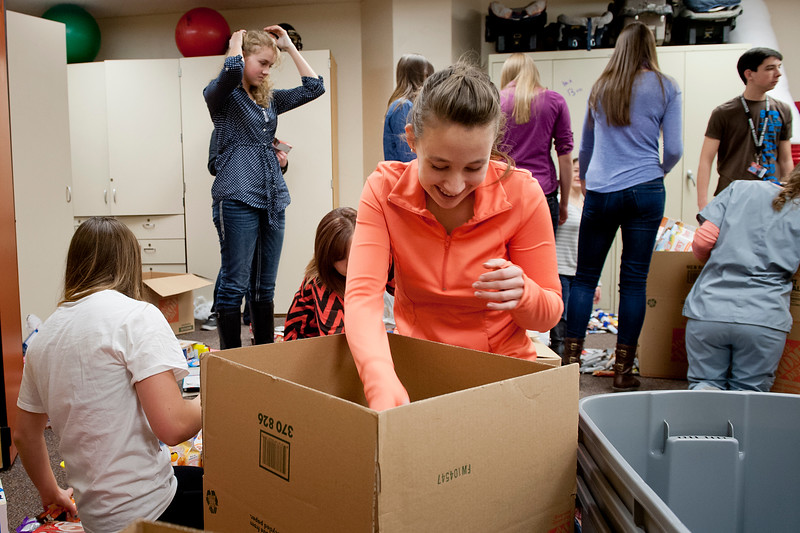 """Brianna Barker stuffs boxes full of food for kids in our area that go home hungry over the weekends. The HOSA club is putting together """"Warrior Packs"""" to end hunger in Utah. At Weber High School, On February 5 2014. (Brian Wolfer Special to the Standard-Examiner)"""