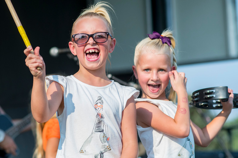 Kaylee Coles (left) and her little sister Maddie get up on stage and play with band Hearts Of Steele, at  Roy Days 2017 on August 3, 2017. The family goes to the event every year as a tradition.