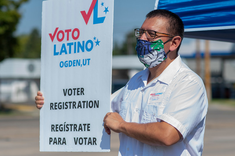 Voto Latino Ogden held a registration event at the Rancho Market in Ogden. On August 29,2020. Enrique Romo holds up signs for the cars passing on 12th street.