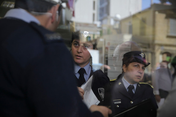 CYPRUS, Nicosia : Policewomen monitor as people queue up outside a Laiki bank branch in the Cypriot capital, Nicosia, on March 28, 2013, as they wait for the bank to open after an unprecedented 12-day lockdown