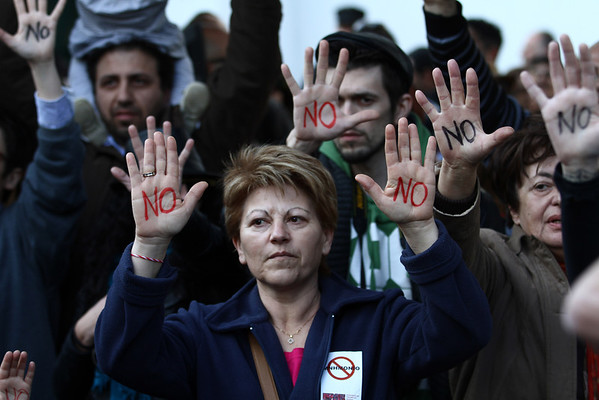 "Cypriots show their palms reading ""No"" during a protest against an EU bailout deal outside the parliament in Nicosia on March 18, 2013."