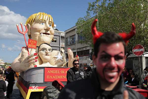 Cypriots walk past a papier-maché statue caricaturing German Chancellor Angela Merkel and President of Cyprus Nikos Anastasiadis, in an annual carnival in the southern city of Limassol.