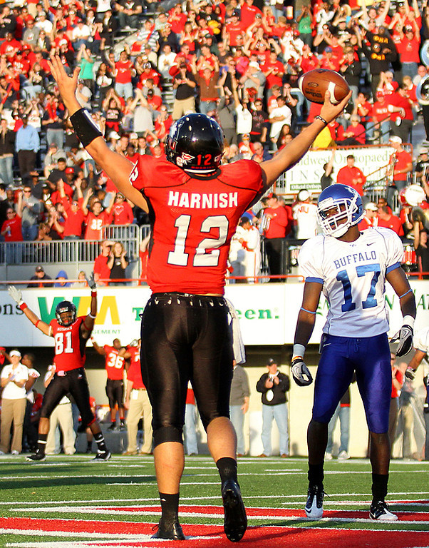 Erik Anderson | The Northern Star<br /> Northern Illinois University quarterback Chandler Harnish raises his arms to the crowd after scoring a touchdown Saturday, October 16, 2010 at Brigham Field in Huskie Stadium. The Huskies would go on to defeat the Bulls 45-14.