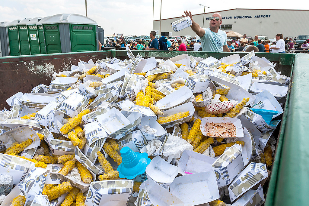 Erik Anderson | The Northern Star<br /> A man throws away a corn cob into a pile of garbage Saturday, August 25, 2012 during DeKalb's Corn Fest held from Friday through Sunday at the DeKalb Taylor Municipal Airport.