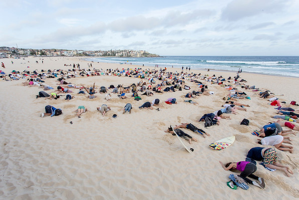 Protesters stick their head in the sand as a symbolic imitation of the Prime Minister of Australia Tony Abbott's refusal to place climate change on the G20 agenda