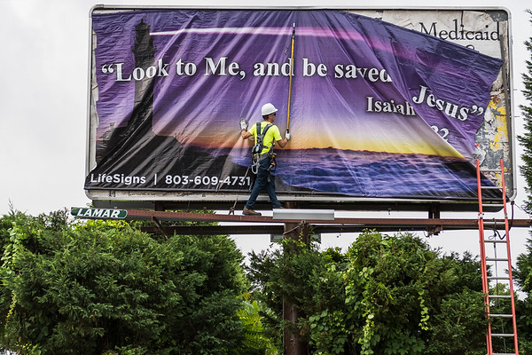 Jim Matthews of Lamar Adverting Company installs a billboard on the corner of Blanding and Harden street in Columbia, SC on June 4, 2019. John A. Carlos II / Special to The Post and Courier