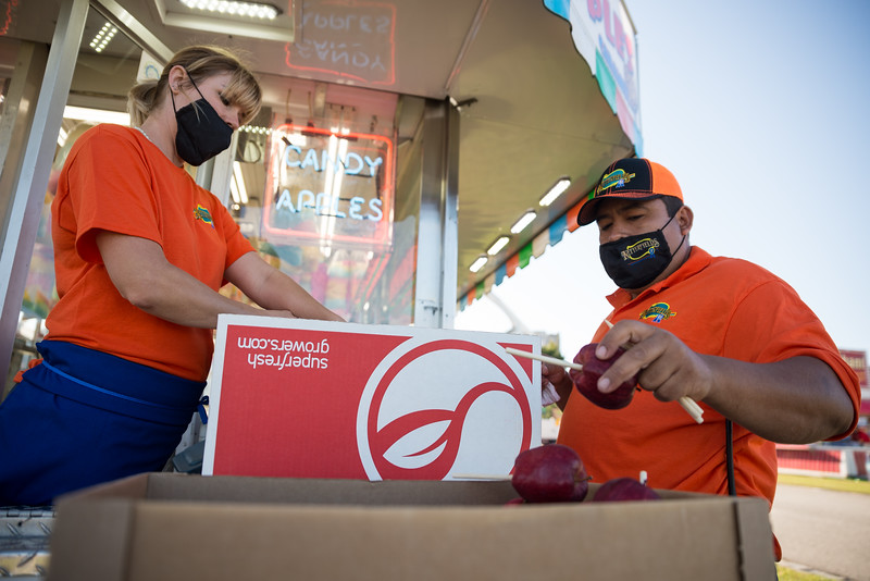 Netterfields employees Jessica Capps and Peter Moreno, put sticks into apples before there candied on the opening day of the drive-thru State Fair on Monday Oct. 19. John A. Carlos II / Special to The Post and Courier