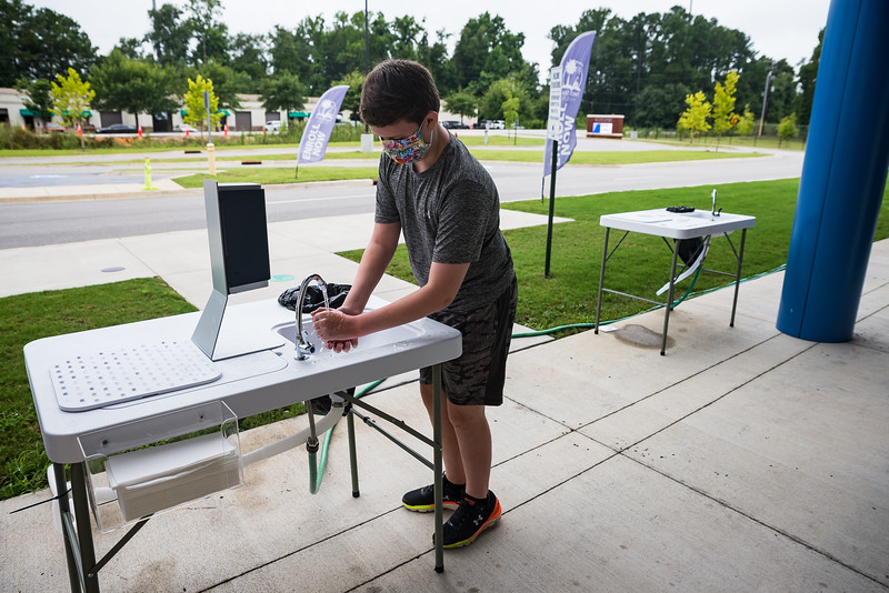 A student at East Point Academy, on July 30, uses a newly installed handwashing station, all students are required to wash their hands before entring the building. John A. Carlos II / Special to The Free Times