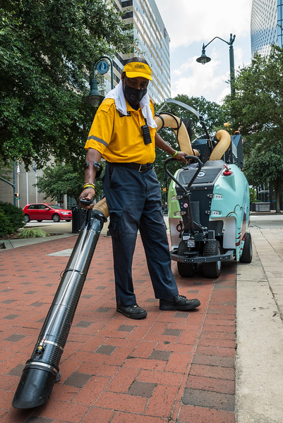Herman Green a downtown ambassador for the City Center Partnership, clean an area outside of Boyd Plaza on July 17, 2020. John A. Carlos II / Special to The Free Times