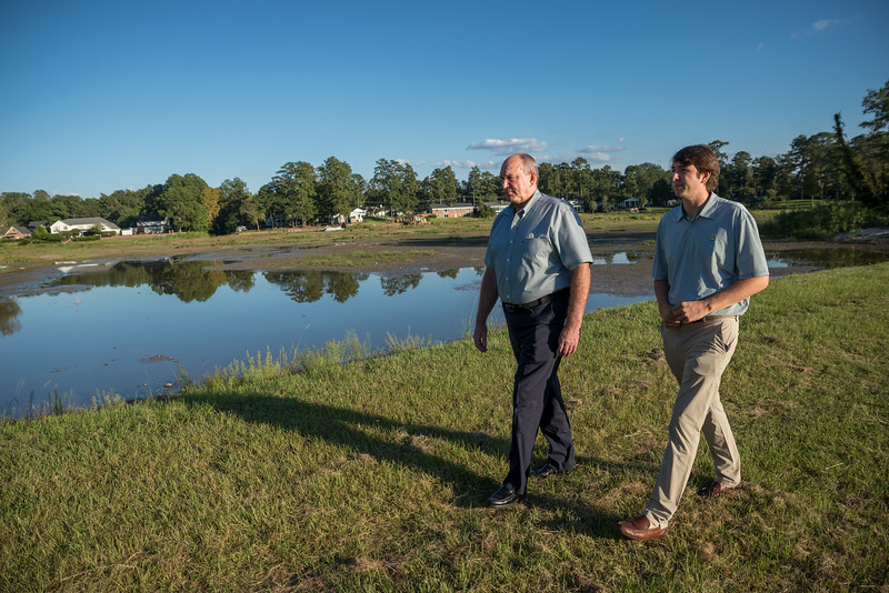 Elliott Powell and Austin Elliott Powell recall personal 2015 flood stories on the bank of Lake Katherine on Oct. 2, 2020. John A. Carlos II / Special to The Post and Courier