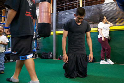 A young boxer takes a break in between sets of pushups.