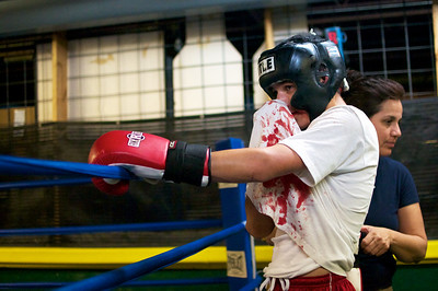 One of the young boxers tries to stop his nose from bleeding after sparring with another participant.