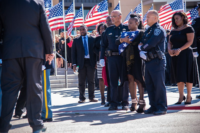 Nola Thomas holds a folded flag as she watches her husband's casket being placed in a hearse following a celebration of life service at Rez.Church in Loveland for officer Yuri Thomas, of the Johnstown Police Department on Monday, September 24, 2018.