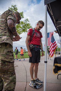 Mike Lavelle weighs in before the start of the Colorado Run, a 10K  race beginning at Cottonwood Glen Park on Monday, May 28, 2018.  Lavelle participated in the Ruck March, carrying a 35-pound pack for the duration of the race.