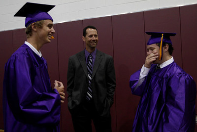 Montgomery High School graduates Casey Kox, left, and Ryan Cross, right, have a conversation with head football coach John Bolfing during the school's commencement ceremony Saturday at Reed Arena in College Station. (text by Eric Swist)