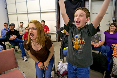 Two young fans scream at the wrestlers during a tense moment in the match.