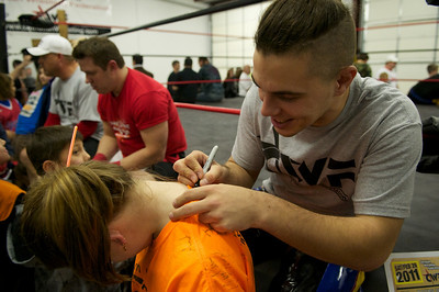 A fan gets her shirt signed by Earl Ray at the end of the night as she collects autographs from all the wrestlers.
