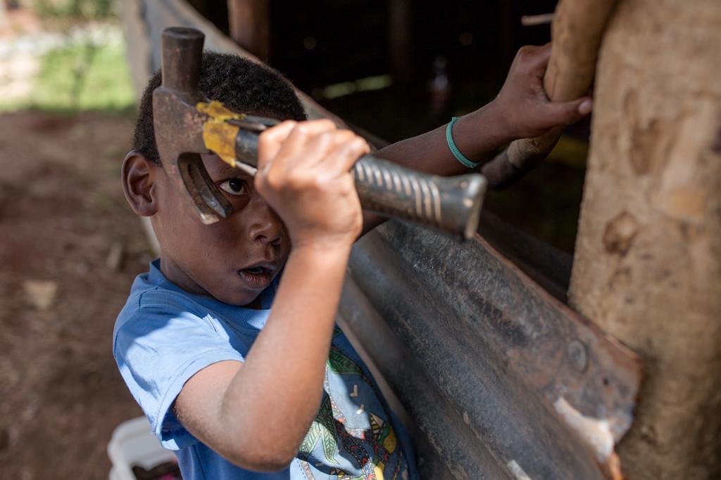 Alosi Vhavathiti helps to repair his house. Nasaibitu village, Nayavu district, Viti Levu, Fiji.