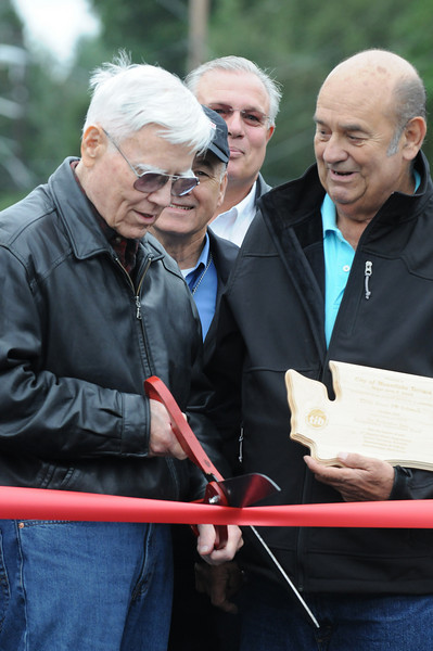 For the Enterprise/John Kossik<br /> The catalyst behind the 230th Street SW Reconstruction project in Mountlake Terrace Pat McMahan cuts the ribbon at 230th Street SW Reconstruction Ribbon Cutting Event on Saturday as Mayor Jerry Smith looks on.