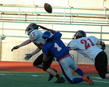 For the Enterprise/John Kossik Vikings reciever Davie Beeks misses a pass in the second half while being double-covered by Cavs Blake Kaweiwahea and  Jake Early