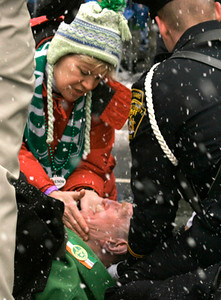 Regis Mooney, 78, bottom, collapses at the St. Patricks Day parade held in downtown Rochester, NY. Mooney has marched in the parade as St. Patrick for 18 years. Photo © by Nicole Jarrett