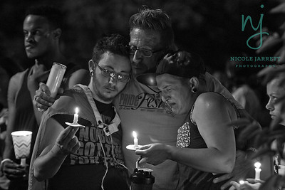Skailer Russell, 28, (left) and Aiden Povis, 27 (right) of Fairview Heights, IL are comforted by Gary Goldberg (center) of O'Fallon, IL at a candlelight vigil to remember those killed and wounded at Pulse Nightclub in Orlando Florida. The vigil was held at the Transgender Memorial Garden in St. Louis, MO on June 12, 2016.