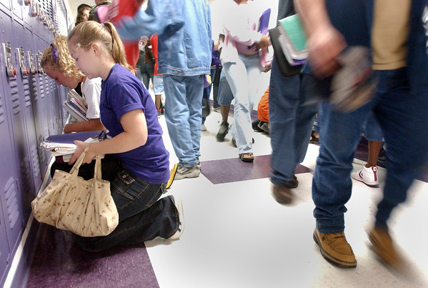 "9:58 A.M. -- Newton High School juniors, Kayla Bishop,  16, left, and Heidi Davis, 16, kneel down to pray for nine seconds in front of their lockers Friday morning at Newton High School. Members of the Fellowship of Christian Athletes paricipate in the ""nine second kneel down"" between second and third periods on game days.<br /> PHOTO/SCOTT ESLINGER                       OCT 1, 2004"