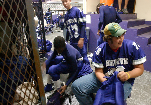 5:30 p.m. -- Newton High School lineman Marcus Bean, 17, right, inserts pads into his pants Friday evening while getting dressed for the game against San Augustine.<br /> PHOTO/SCOTT ESLINGER                       OCT 1, 2004
