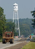 10:45 a.m. -- A logging truck heads toward the water tower emblazoned with the school logo that looms over downtown Newton Friday morning.<br /> PHOTO/SCOTT ESLINGER                       OCT 1, 2004