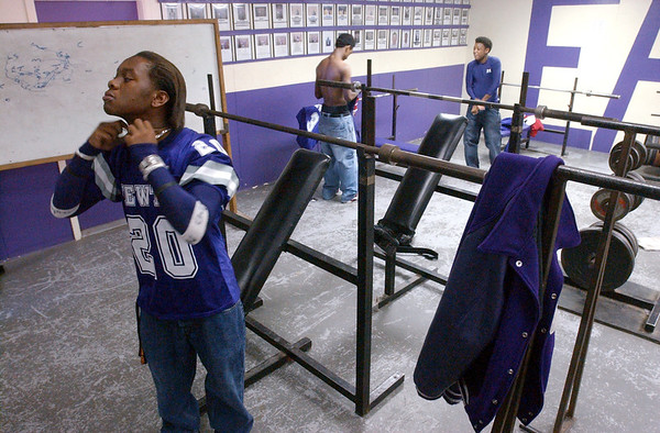 11:00 a.m. -- Newton High School wide receiver Meredith Diggles, 16, adjusts a necklace after putting on his jersey in the locker room during fourth period Friday morning in Newton. After listening to Coach Barbay go over plans for the night's game the players will wear the jerseys for the rest of the day.<br /> PHOTO/SCOTT ESLINGER                       OCT 1, 2004