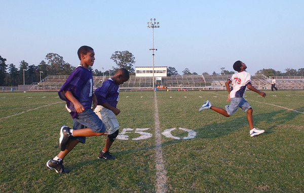 6:10 p.m. -- Brenten Spikes, 10,  left to right, D.J. Dean, 9, and Stephon Johnson, 11, all of Newton,  run a foot race on the field at Newton High School's Singletary Stadium Friday evening about an hour and 20 minutes before kick-off.<br /> PHOTO/SCOTT ESLINGER                       OCT 1, 2004