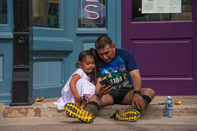 A Colorado Marathon participant sits with his daughter upon completion of the race in Old Town Square, Fort Collins on Sunday, May 7, 2017.