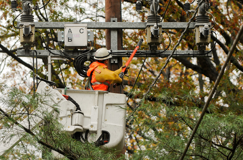 10.30.12- BALTIMORE,  MD- Power company workers from BGE and ComEd, a Excelon Company, shown here grounding the overhead lines in order to fix the lines brought down by winds along Providence Road in Baltimore County. (Maximilian Franz/The Daily Record).