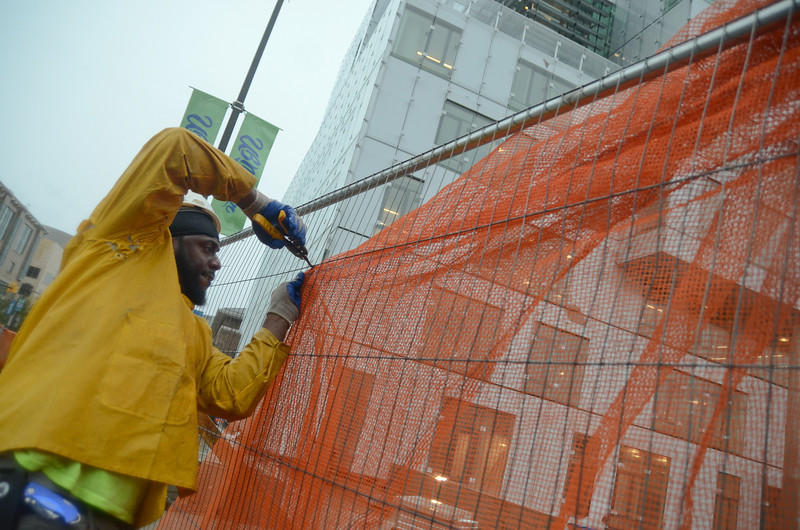10.29.12- BALTIMORE,  MD- Calvin Harrid, a construction worker with Whiting Turner, takes down a wind barrier along the construction fence that surrounds the site at the new University of Baltimore law school building.  (Maximilian Franz/The Daily Record).