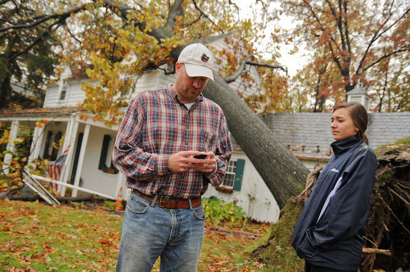 10.30.12- BALTIMORE,  MD- A large Oak tree fell on the home and lifted the car of owner Andy Smith on Hillen Road near Towson. The Tree fell during high winds around 6:30 pm on October 29th, 2012 around the time Hurricane Sandy made landfall. The Family was in the home but no one was injured. Here Andy stands outside with his daughter Alexis George while waiting for his insurance adjustor. (Maximilian Franz/The Daily Record).