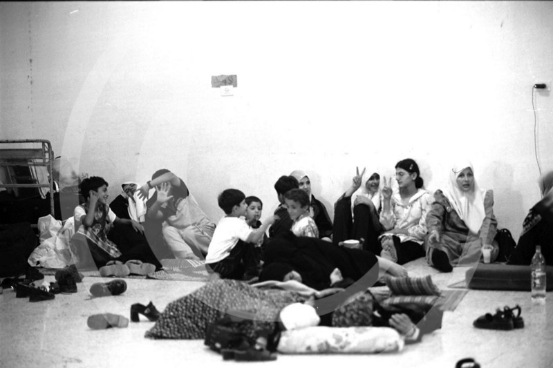 Families rest for days on makeshift mats inside of the Israeli border patrol building while waiting for permission to cross over into Jordan.