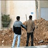 Palestinians looking at a new roadblock developed in the center of Ramallah, March 2002.