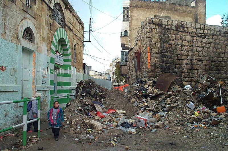 During one of the Israeli invasions into Hebron, the IDF destroyed many of the historical homes located in the center of Hebron.  One of the homes is on the right, while children attempt to go to school walking through the destruction.