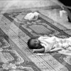 A baby sleeps while the parents wait to obtain permission to cross over into Jordan at the Israeli/Jordanian checkpoint.