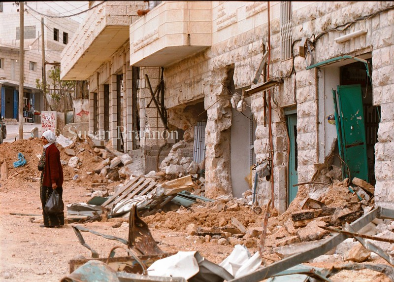 A woman stands outside of her destroyed home after the First Israeli incursion into Bethlehem.  Many homes and streets were destroyed while the Palestinians were not allowed to go outside.