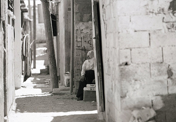 A woman sitting outside of her home in the Gaza Strip selling some wares.