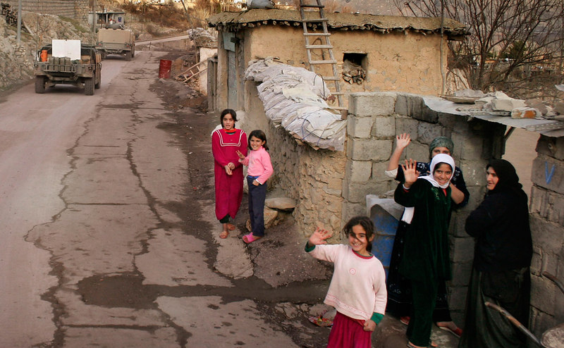 Kurdish women and children wave to soldiers as a convoy passes through their small village in Irbil Province.