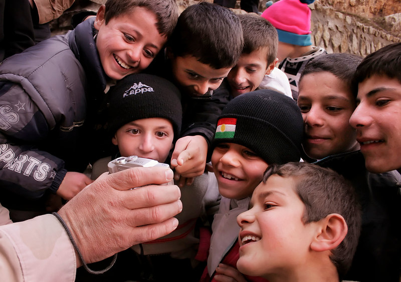 Kurdish boys look in amazement at a picture of themselves displayed on the back of a digital camera.